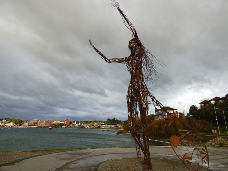 A piece of art in Puerto Varas, as she stretches her arms out towards the water and the 2 volcanoes that loom behind it.