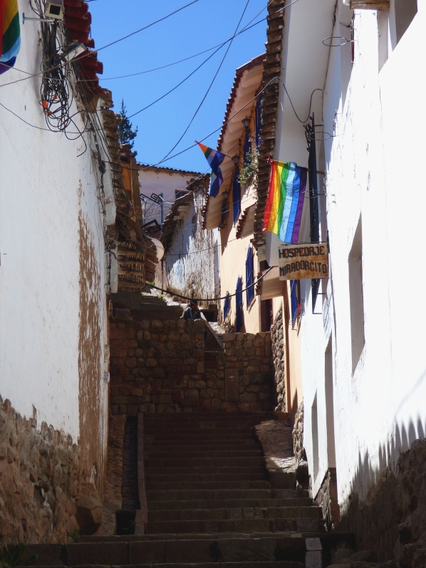 An average side street in Cusco, with part road, part stairs. Also, Cusco's regional flag!