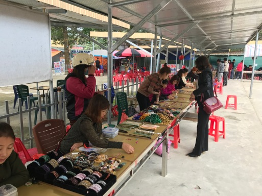 A small corner of the market, women make deals to sell the gems cut, uncut, in bracelats, and in necklaces.